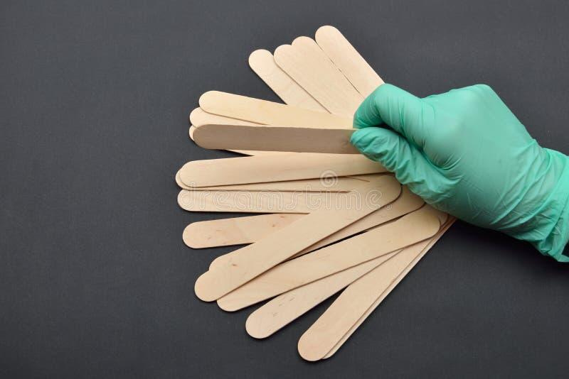 De schoonheidsspecialisten overhandigen met groene handschoen houdend houten spatel voor was stock fotografie