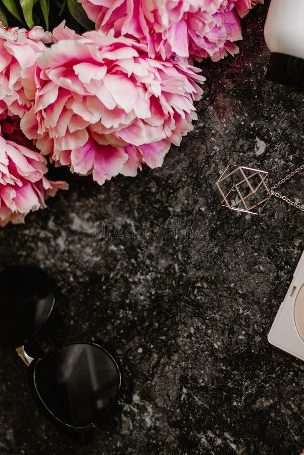 De schoonheidsvlakte legt met toebehoren, parfum, schoonheidsmiddelen en pioenen op een donkere marmeren achtergrond stock afbeelding