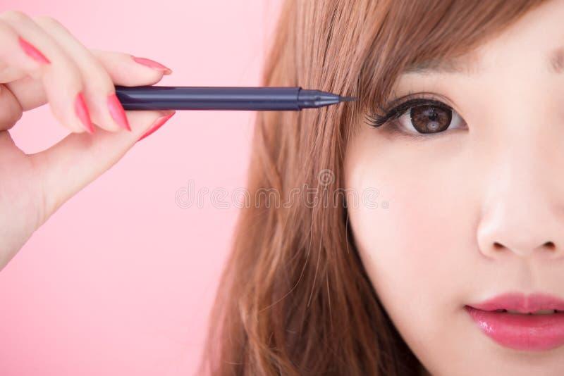 De schoonheidsvrouw neemt eyeliner royalty-vrije stock foto's