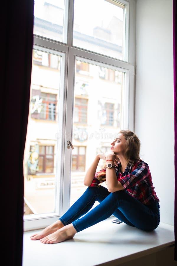 De schoonheidsvrouw ontspant op vensterbankachtergrond royalty-vrije stock afbeeldingen