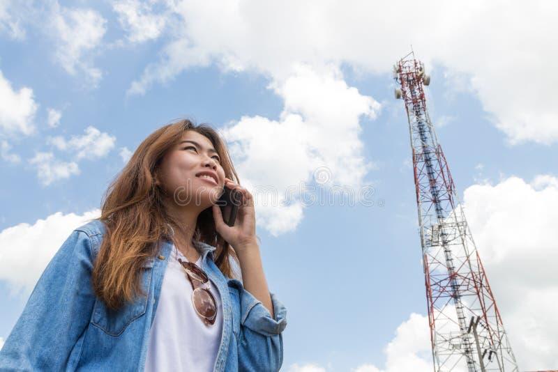De schoonheidsvrouwen gebruiken slim telefoongesprek en satellietcommunicatietoren stock fotografie