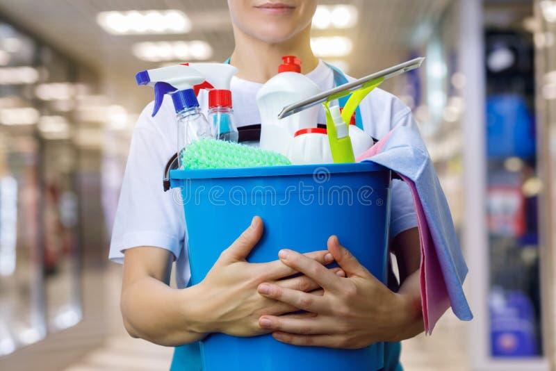 De schoonmaakster met een emmer en schoonmakende producten is stock afbeelding