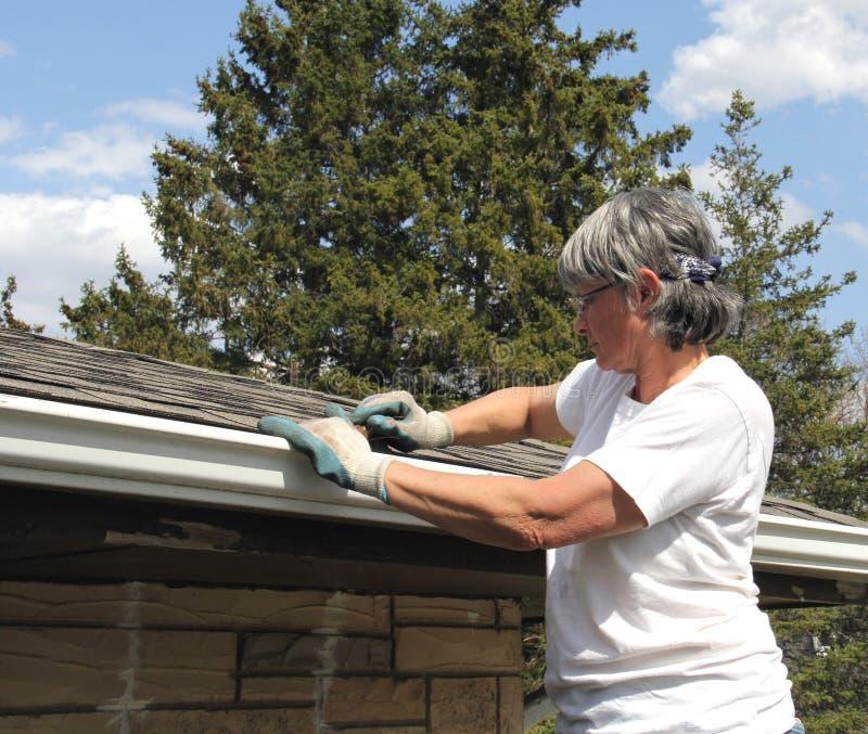 De schoonmakende dakgoten van de vrouwenlente stock afbeeldingen