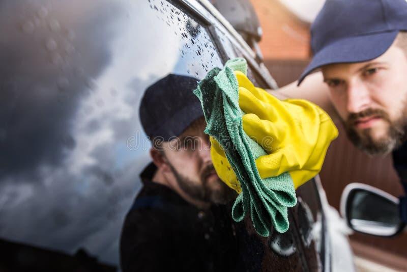 de schoonmakende dienst De mens in eenvormige en gele handschoenen wast een venster van het autoglas in een autowasserette stock foto