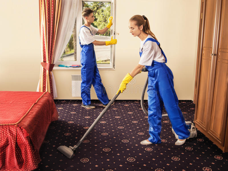De schoonmakende dienst met beroepsuitrusting tijdens het werk stock afbeelding