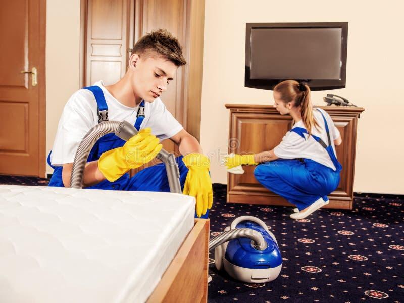 De schoonmakende dienst met beroepsuitrusting tijdens het werk stock fotografie