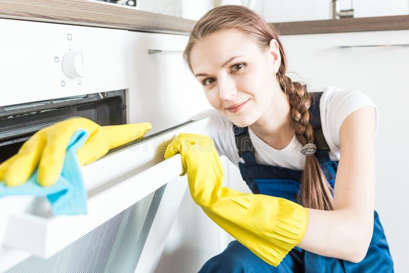 De schoonmakende dienst met beroepsuitrusting tijdens het werk het professionele kitchenette schoonmaken, bank chemisch reinigen, stock fotografie