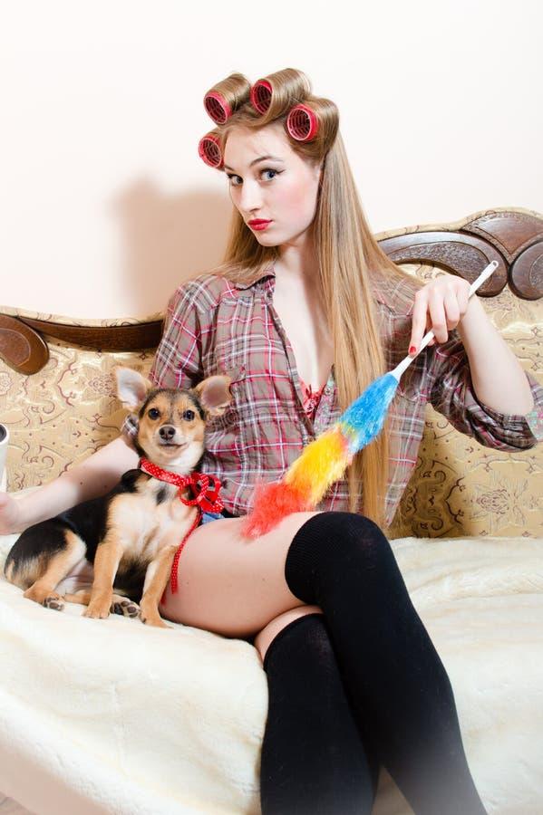 De schoonmakende dienst: mooi weinig hond met rode lintzitting met pinupmeisje in bed die ernstig camera bekijken stock foto's
