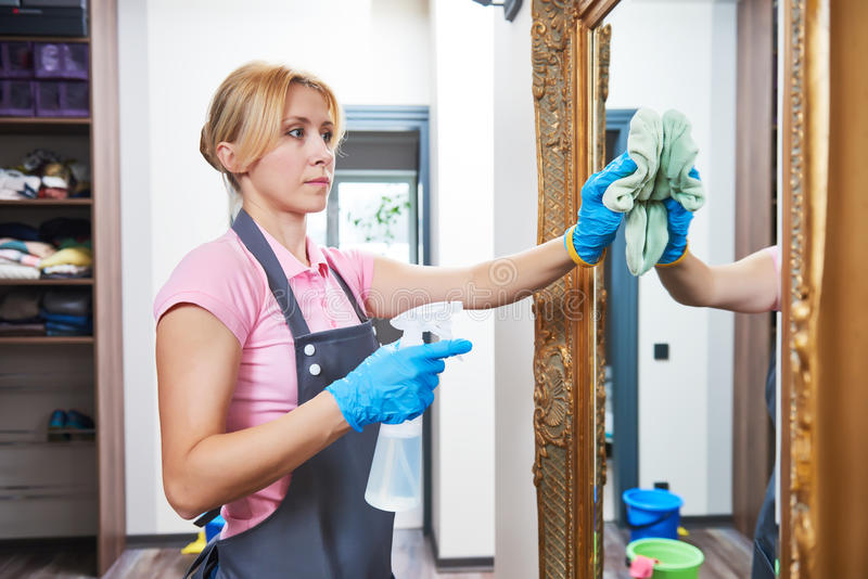 de schoonmakende dienst Spiegel van de vrouwen de afvegende muur thuis stock afbeeldingen