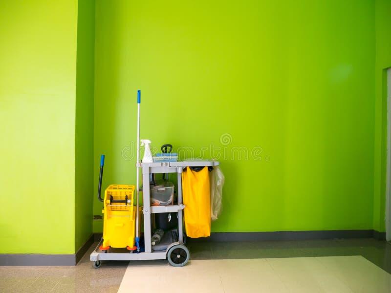 De schoonmakende hulpmiddelenkar wacht op het schoonmaken Emmer en reeks van het schoonmaken van materiaal in het bureau stock foto