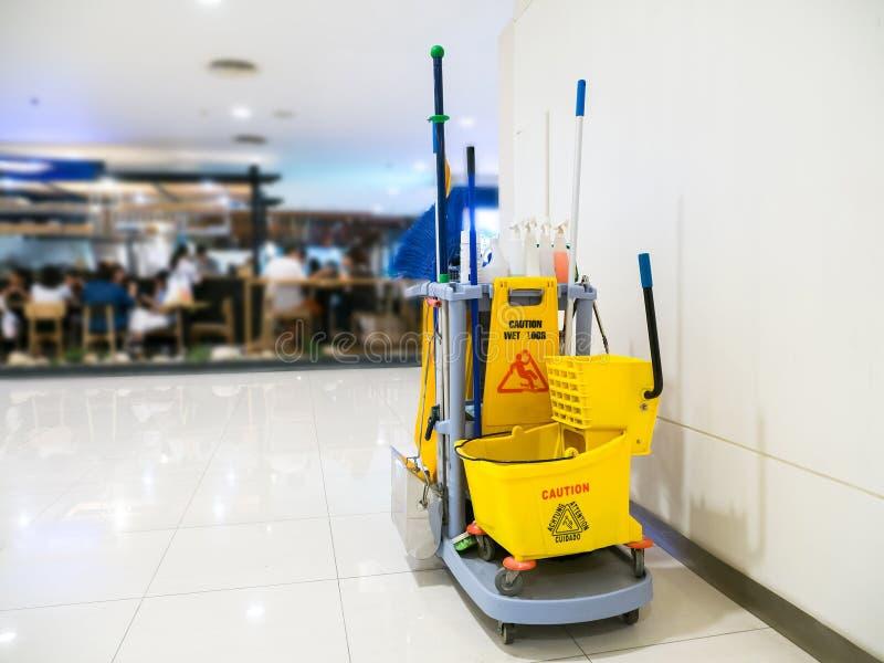 De schoonmakende hulpmiddelenkar wacht op het schoonmaken Emmer en reeks van het schoonmaken van materiaal in het warenhuis stock afbeeldingen