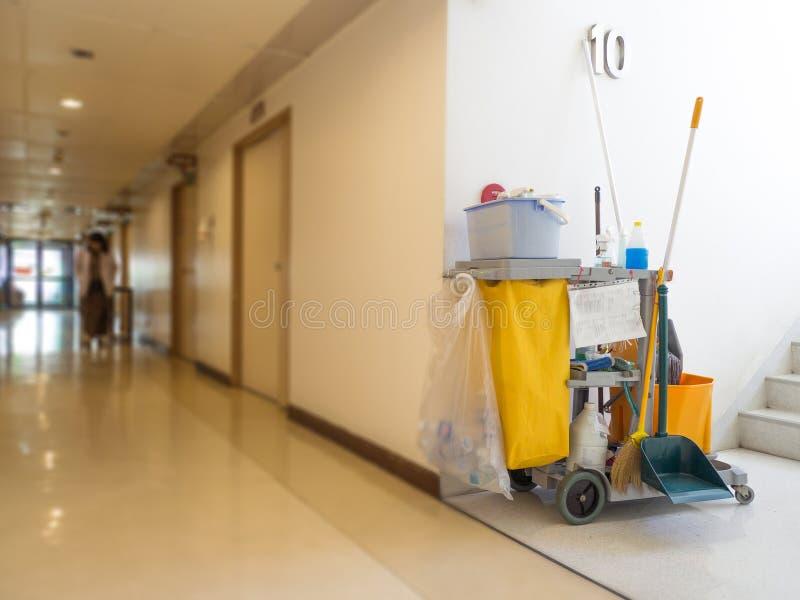 De schoonmakende hulpmiddelenkar wacht op meisje of reinigingsmachine in het ziekenhuis Emmer en reeks van het schoonmaken van ma stock afbeelding