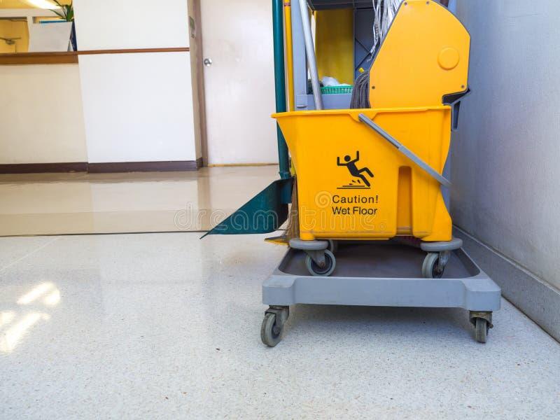 De schoonmakende hulpmiddelenkar wacht op meisje of reinigingsmachine in het ziekenhuis De waarschuwingsborden die in proces de v stock fotografie
