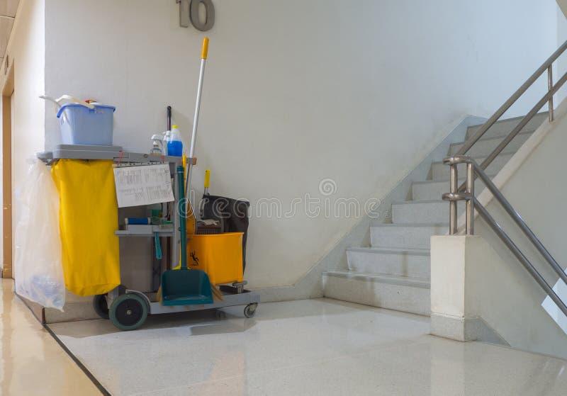 De schoonmakende hulpmiddelenkar wacht op reinigingsmachine Emmer en reeks van het schoonmaken van materiaal in de flat de portie stock afbeeldingen