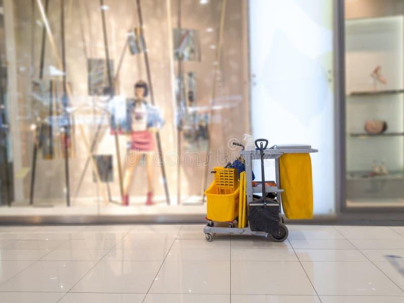 De schoonmakende hulpmiddelenkar wacht op reinigingsmachine Emmer en reeks van het schoonmaken van materiaal in het warenhuis de  royalty-vrije stock afbeeldingen
