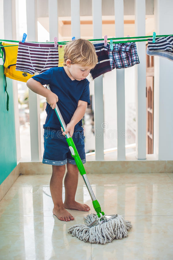 De schoonmakende ruimte van de jong geitjejongen, wassende vloer met zwabber Weinig huishelper Montessoriconcept royalty-vrije stock foto