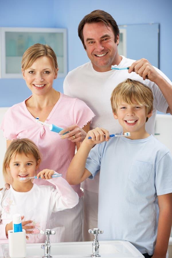 De schoonmakende tanden van de familie samen in badkamers stock afbeeldingen