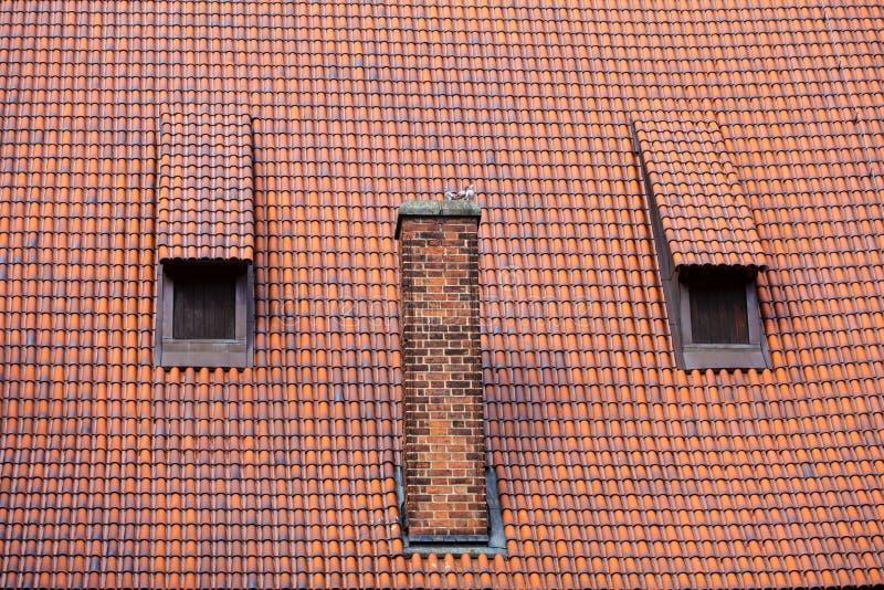 De schoorsteen en de zolderkamer rood tegelsdak van het architectuurdetail stock foto