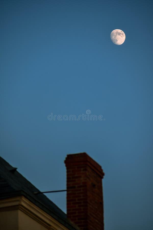 De schoorsteen en het dak unfocused, met de maan op de achtergrond Concept huis en nacht royalty-vrije stock foto's