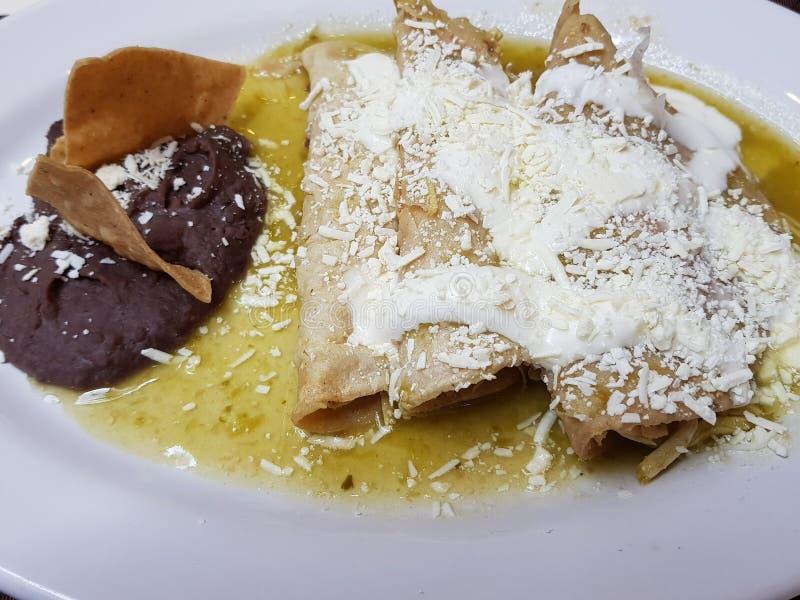 de schotel met groene enchiladas en refried bonen, typisch Mexicaans voedsel royalty-vrije stock fotografie