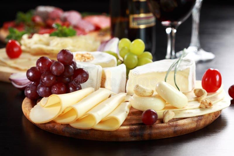 De schotel van de kaas en van de salami met kruiden stock fotografie