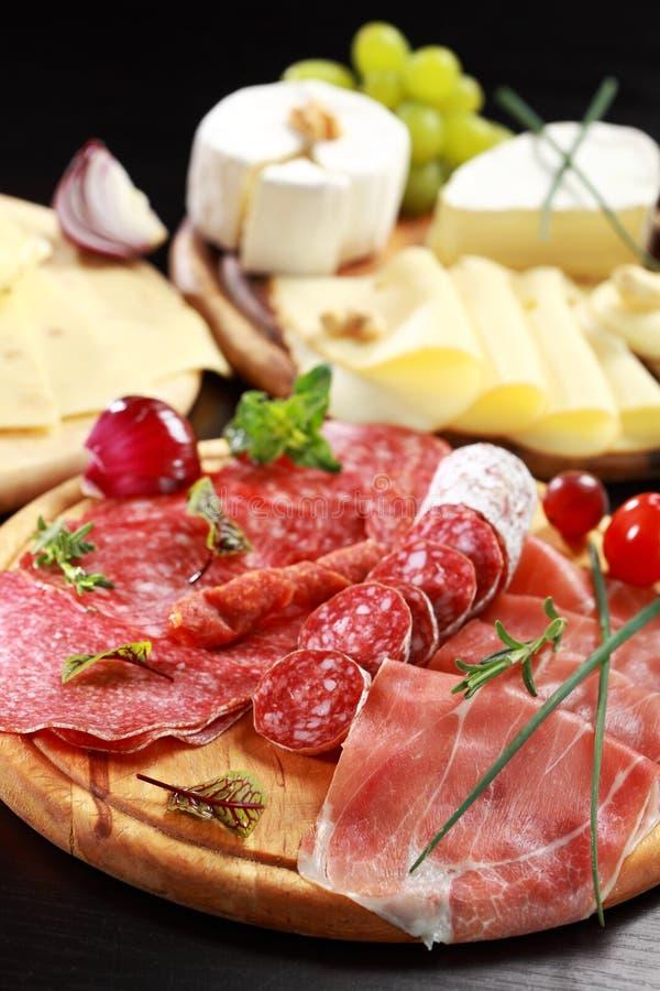 De schotel van de salami en van de kaas met kruiden royalty-vrije stock foto