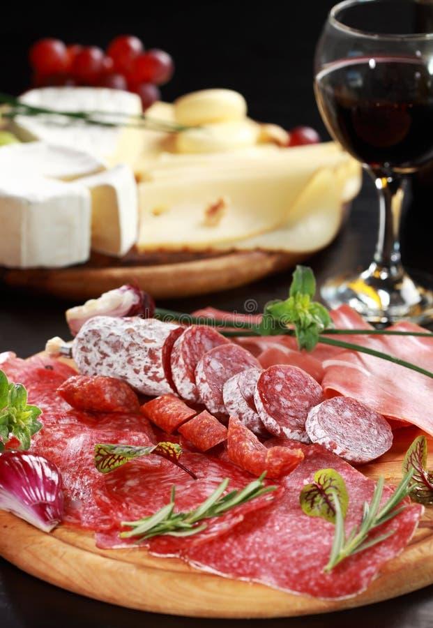 De schotel van de salami en van de kaas met kruiden royalty-vrije stock fotografie