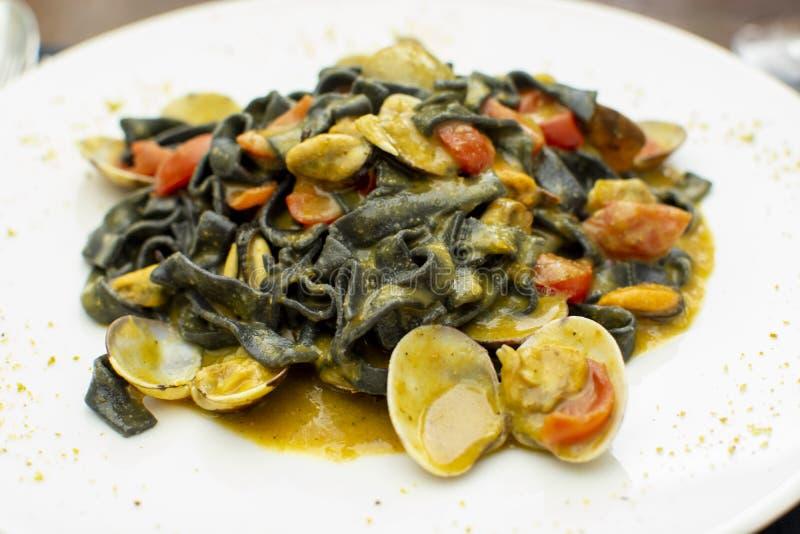 De schotel van zeevruchtendeegwaren, Italiaanse zwarte fettuccini met vongoletweekleppige schelpdieren en mosselen stock foto