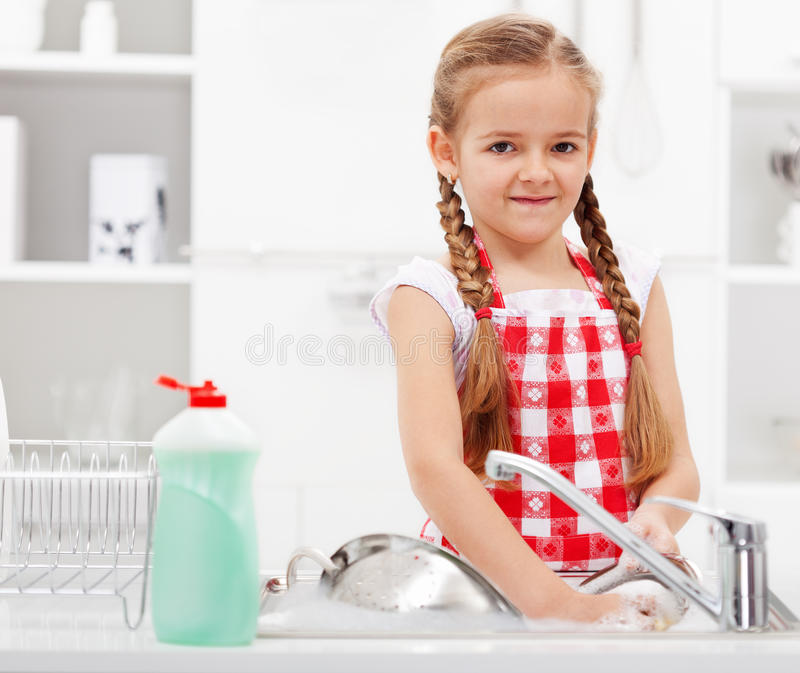 De schotels van de meisjewas in de keuken stock fotografie