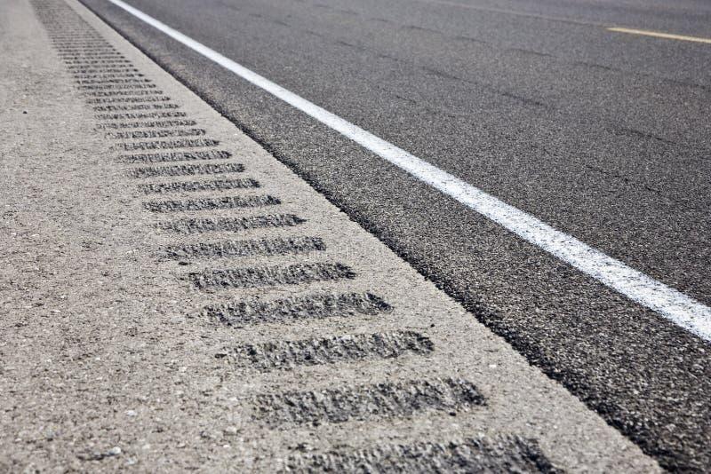De schouder van de rijweg mompelt stroken stock afbeelding