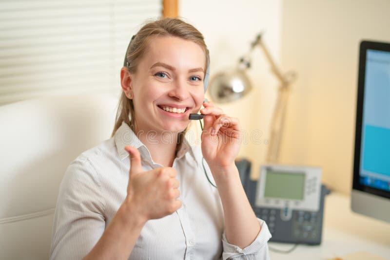 De schreeuwen die van de meisjesverzender met de telefoon werken In het call centre, de glimlach en het positief stock afbeeldingen