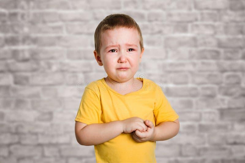 De schreeuwende babyjongen in een gele T-shirt behandelt zijn gezicht met handen en schreeuwen, studio op bakstenen muurachtergro royalty-vrije stock foto
