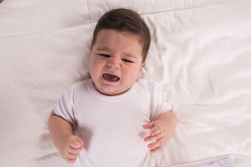 De schreeuwende Jongen van de Baby Nieuw - geboren die kind en hongerig in bed wordt vermoeid Childre royalty-vrije stock foto's