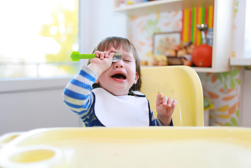 De schreeuwende peuterjongen wil niet eten stock afbeelding