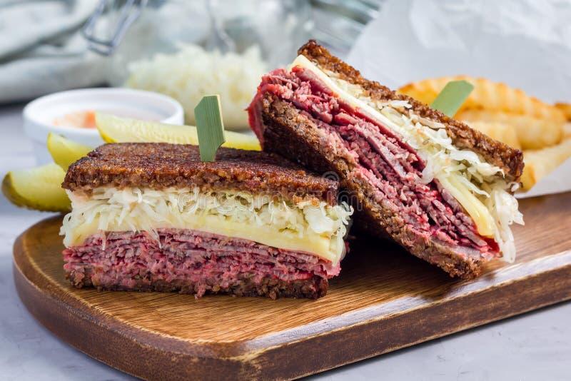 De schrijver uit de klassieke oudheid reuben sandwich, met dillegroenten in het zuur wordt gediend, horizontale die chips, royalty-vrije stock afbeelding