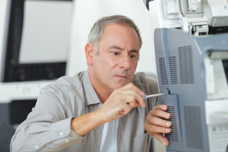 De schroevedraaier van de Mandholding voor het bevestigen van printer royalty-vrije stock afbeelding