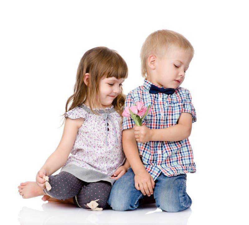 De schuwe jongen geeft aan het meisje een bloem Op witte achtergrond royalty-vrije stock afbeeldingen