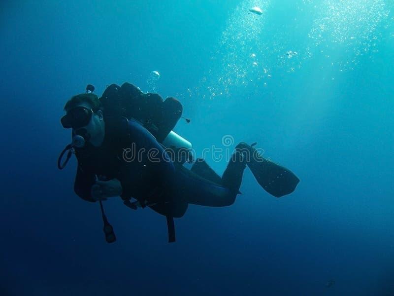 De scuba-duiker met volledig materiaal is onderwater Zonlicht en bellen stock foto's