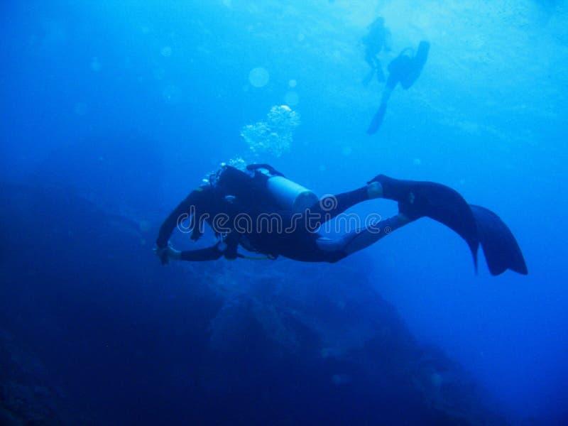 De scuba-duiker met volledig materiaal is onderwater Zonlicht en bellen Twee scuba-duikers zijn op de achtergrond stock afbeeldingen