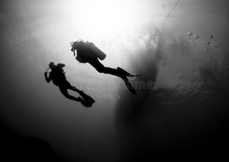 De scuba-duikers silouetted door zonbal stock foto