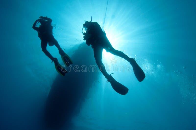 De scuba-duikers van Sihlouetted stock afbeeldingen