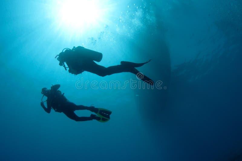 De scuba-duikers van Sihlouetted royalty-vrije stock afbeelding