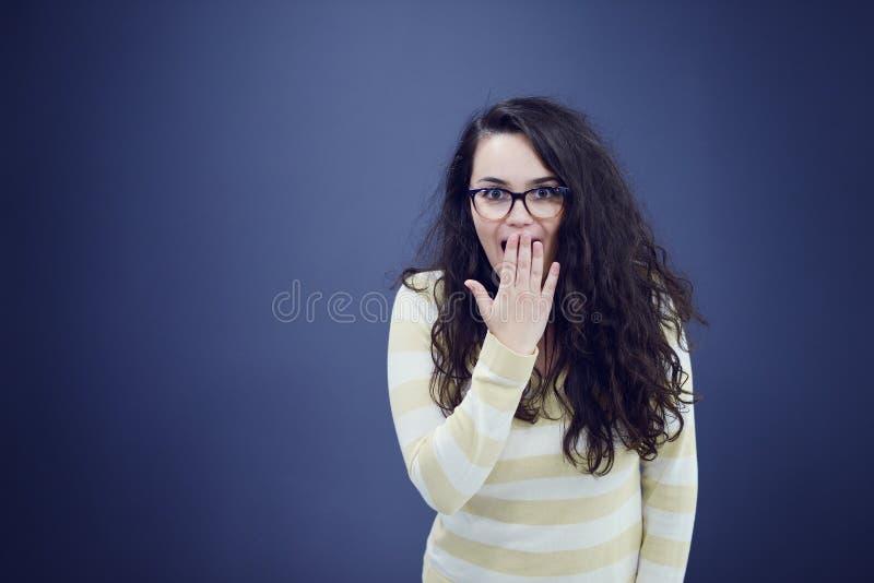 De secretaresse of de bedrijfsvrouw met verrast kijkt op haar die gezicht over donkere achtergrond wordt geïsoleerd stock fotografie