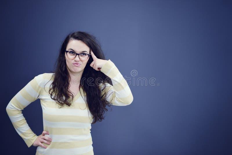 De secretaresse of de bedrijfsvrouw met verrast kijkt op haar die gezicht over donkere achtergrond wordt geïsoleerd stock foto