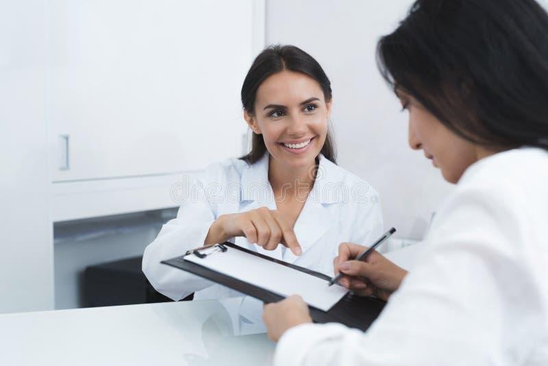 De secretaresse in een medische kliniek helpt geduldige volledig de noodzakelijke vormen alvorens behandeling te beginnen royalty-vrije stock fotografie