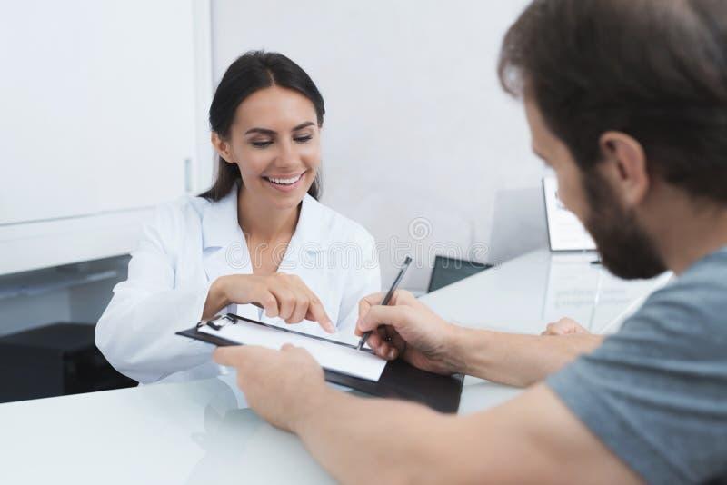 De secretaresse in een medische kliniek helpt geduldige volledig de noodzakelijke vormen alvorens behandeling te beginnen stock foto's