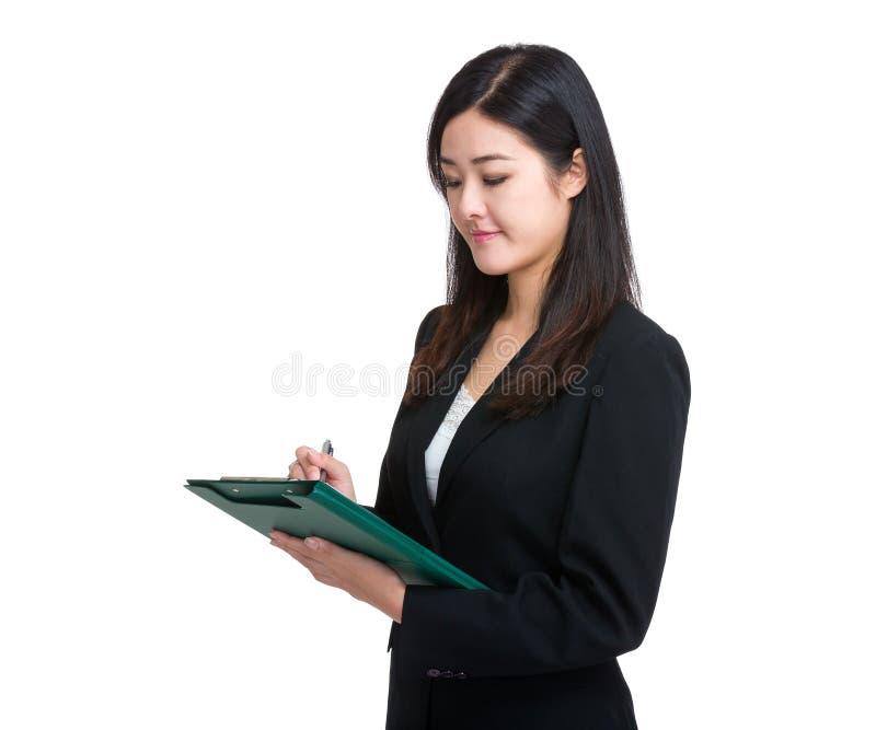 De secretaresse schrijft op klembord royalty-vrije stock afbeelding