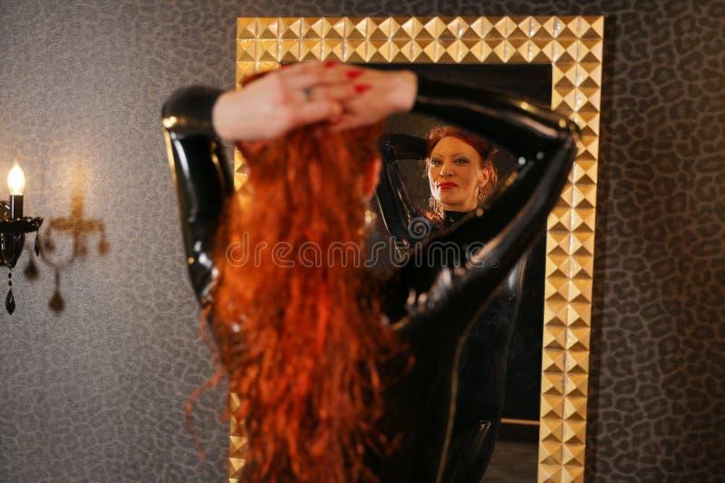 De seksuele vrouw die van het amuletroodharige zwart latexrubber dragen catsuit en de spiegel in donkere ruimte bekijken royalty-vrije stock afbeelding