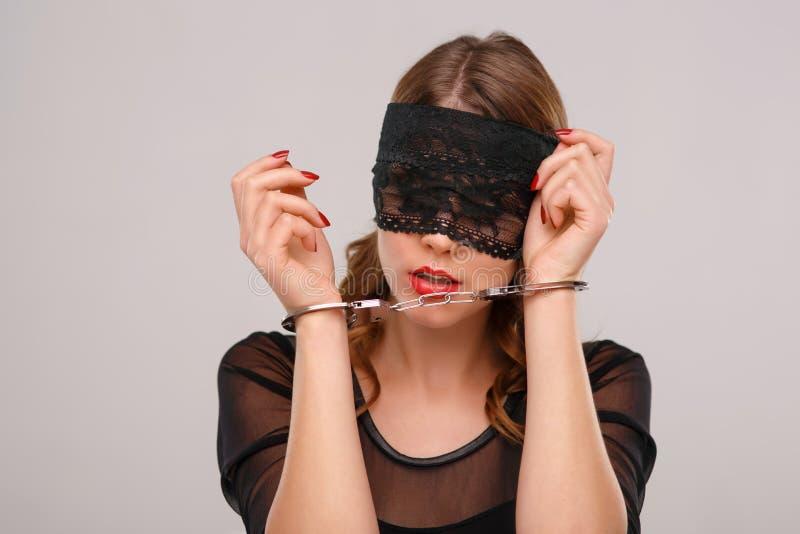 De seksuele vrouw in eyeshade sloot met handcuffs stock foto's