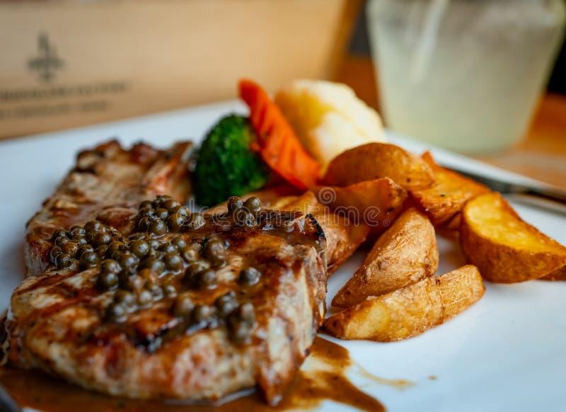 De selectieve die nadruk op lapje vlees met saus wordt bedekt en de peper dienen met gebraden aardappel en gestoomde wortelen, bl stock foto's